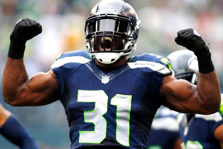 Seattle Seahawks strong safety Kam Chancellor (31) celebrates a hit on St. Louis Rams' Stedman Bailey in the first half of an NFL football game, Sunday, Dec. 29, 2013, in Seattle. (AP Photo/John Froschauer)