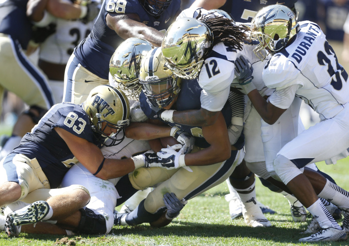 The Akron defense led by linebacker C.J. Mizell (12) and cornerback Martel Durant (32) stop Pittsburgh running back James Conner (24) on a run in the second quarter of the NCAA college football game on Saturday, Sept. 27, 2014 in Pittsburgh. Akron won 21-10. (AP Photo/Keith Srakocic)