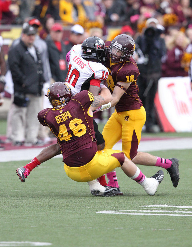 DL Blake Serpa and S Tony Annese combine for a tackle against NIU (Courtesy of CMU Athletics)