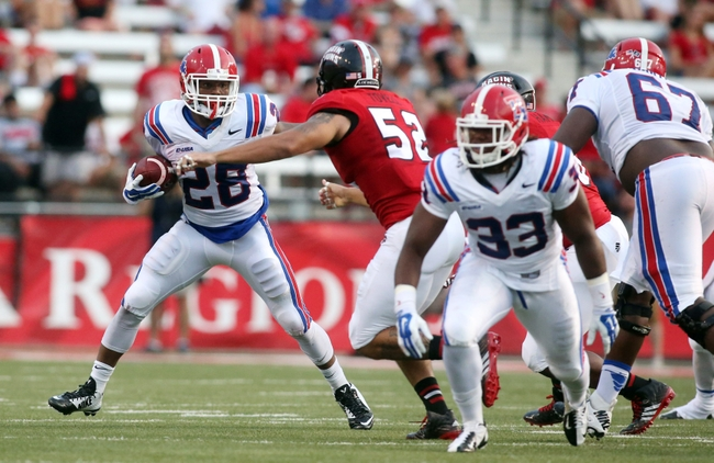 Sep 6, 2014; Lafayette, LA, USA; Louisiana Tech Bulldogs running back Kenneth Dixon (28) carries the ball beside Louisiana-Lafayette Ragin Cajuns defensive end Dominique Tovell (52) in the first half at Cajun Field. Louisiana Tech defeated Louisiana-Lafayette Ragin Cajuns 48-20. Mandatory Credit: Crystal LoGiudice-USA TODAY Sports