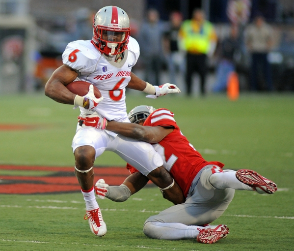 Nov 1, 2014; Las Vegas, NV, USA; New Mexico Lobos running back Jhurell Pressley (6) shakes off the tackle of UNLV Rebels defensive back Mike Horsey (32) during an NCAA football game at Sam Boyd Stadium. New Mexico won the game 31-28. Mandatory Credit: Stephen R. Sylvanie-USA TODAY Sports