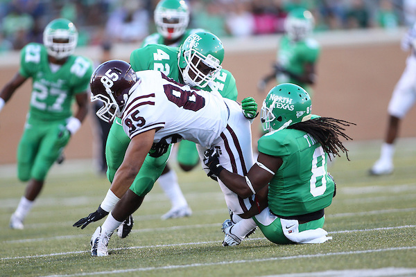 Denton, TX - SEPTEMBER 8: Wayne Ingram #85 of the Texas Southern Tigers is tackled by Chad Polk #42 and Marcus Trice #8 of the North Texas Mean Green at Apogee Stadium in Denton on September 8, 2012 in Denton, Texas. Photo by: Rick Yeatts