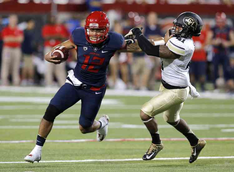 Zona QB Anu Solomon stiff arms a CU defender (Photo Courtesy of AP Photo)