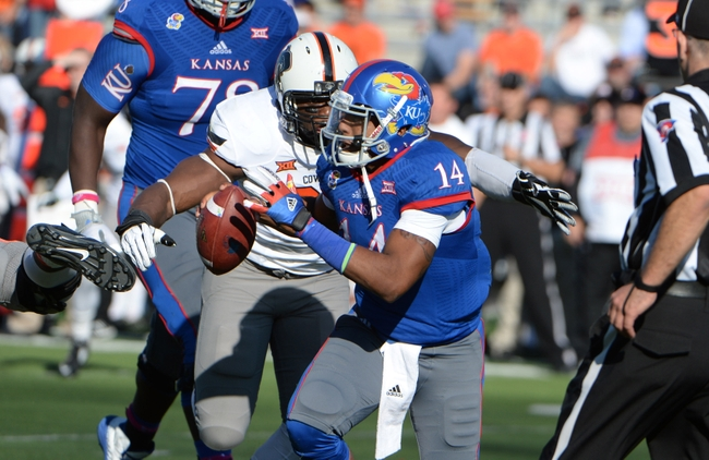 Oct 11, 2014; Lawrence, KS, USA; Kansas Jayhawks quarterback Michael Cummings (14) is sacked by Oklahoma State Cowboys defensive end Emmanuel Ogbah (38) in the first half at Memorial Stadium. Mandatory Credit: John Rieger-USA TODAY Sports