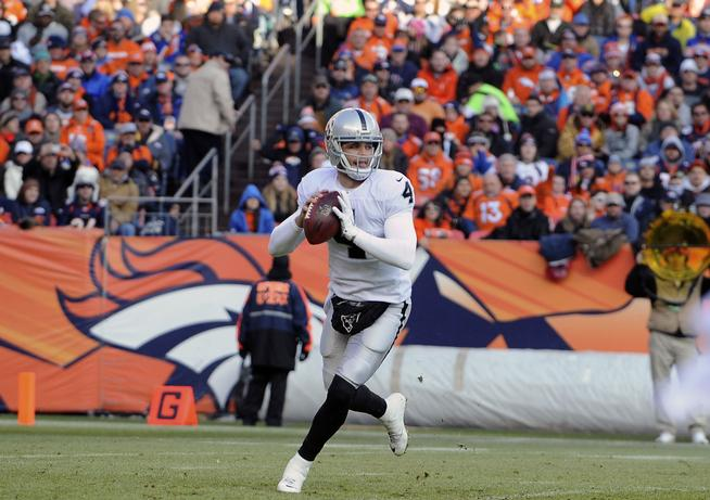 DENVER, CO - DECEMBER 28: Oakland Raiders quarterback Derek Carr rolls out to pass in the second quarter against the Denver Broncos at Sports Authority Field at Mile High in Denver on December 28, 2014. (Photo by Steve Nehf/The Denver Post)