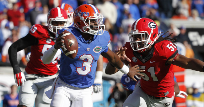 Nov 1, 2014; Jacksonville, FL, USA; Florida Gators quarterback Treon Harris (3) stiff arms as Georgia Bulldogs linebacker Ramik Wilson (51) rushes during the first quarter at EverBank Field. Mandatory Credit: Kim Klement-USA TODAY Sports