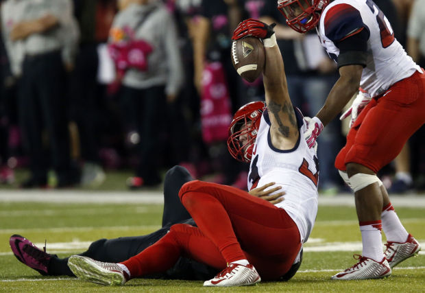 Scooby Wright holds up ball after stripping Marcus Mariota (Photo Courtesy of Kelly Pressnell/Arizona Daily Star)